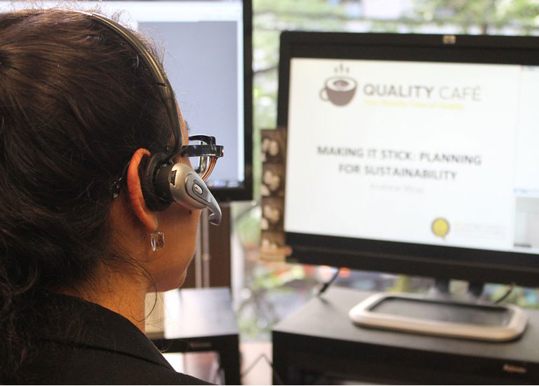 A person wearing a headset and looking at a computer screen.
